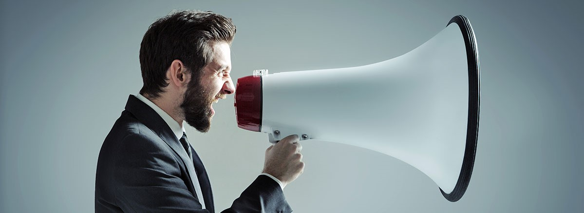 Businessman communicating to a big audience using a loudspeaker